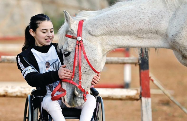 ركوب الخيل يساعد طفلة مصابة بشلل