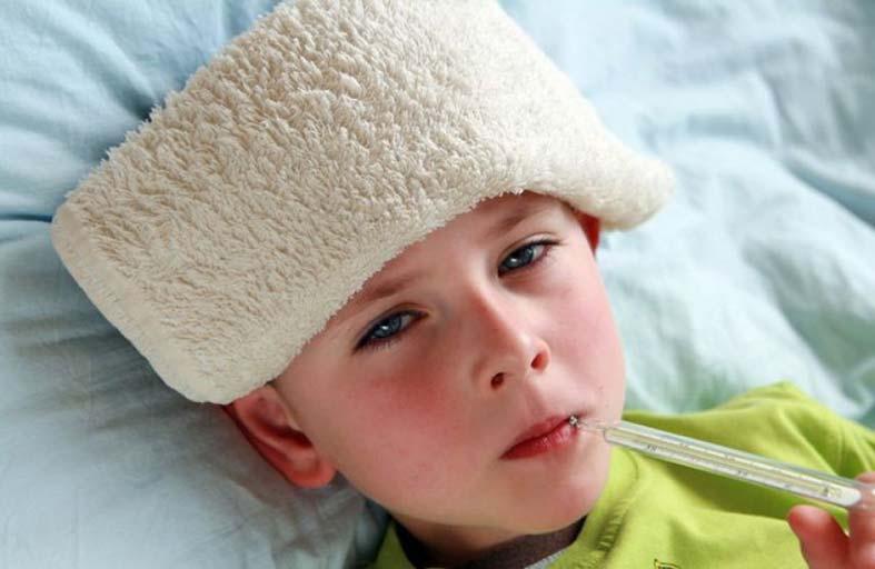 Dečak sa oblogom na glavi za skidanje temperature