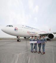 طاقم الخطوط الجوية الماليزية  يحملن لافتة «Visit Malaysia 2020» أمام طائرة في مطار كوالالمبور الدولي في سيبانغ ، ماليزيا. رويترز