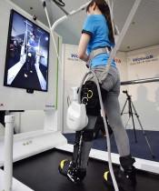 مسؤولة تسويق تستعرض الروبوت (1000 Welwalk WW) الذي انتجته شركة تويوتا موتور اليابانية للمساعدة في إعادة تأهيل المرضى المصابين بالشلل في الاطراف السفلية نتيجة للسكتة الدماغية وغيرها من الأسباب. (ا ف ب)