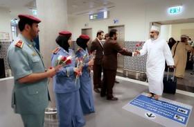 شرطة أبوظبي تستقبل العمانيين في مطار أبوظبي بالورد احتفاء بيومهم الوطني