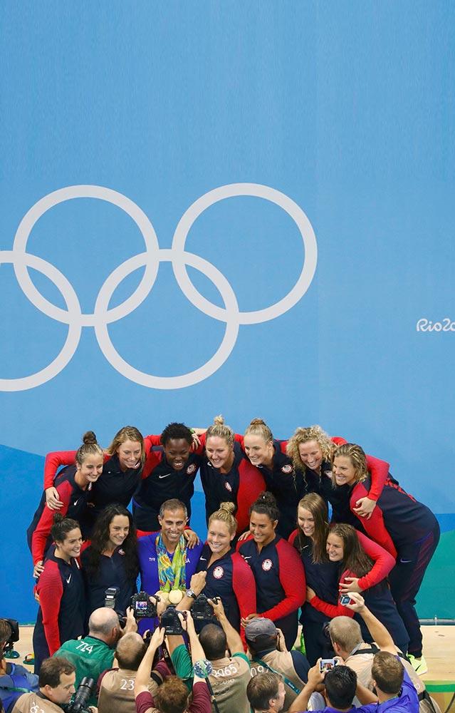 الصحفيون يلتقطون صوراً للفريق الأمريكي لكرة الماء للسيدات مع مدربهم آدم كريكوريان بعد فوزهن بالميدالية الذهبية في دورة الألعاب الأولمبية. (رويترز)