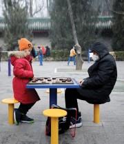 طفل ورجل مسن يلعبان الشطرنج الصيني بحديقة في بكين. ا ف ب