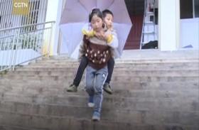 طفلة تحمل شقيقها المعاق يومياً إلى المدرسة