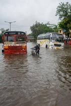 سائق دراجة نارية يدفع دراجته المعطلة بين حافلتين عالقتين خلال هطول الأمطار الموسمية الغزيرة في مومباي. ا ف ب