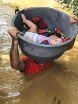 فرد من حرس السواحل يستخدم حوضًا لإجلاء طفل من منزل غمرته الفيضانات في مقاطعة كاجايان، شمال مانيلا. ا ف ب