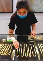 موظفة ترتدي قناع وجه وتقوم بترتيب المجوهرات في متجر للذهب في العاصمة الفيتنامية هانوي. ا ف ب