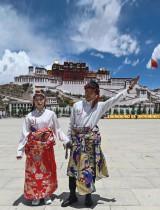 شاب وفتاة يرتديان الزي التقليدي ويقفون أمام قصر بوتالا - الذي صنفته اليونسكو كموقع للتراث العالمي في عام 1994 - في لاسا بمنطقة التبت الصينية ذاتية الحكم. ا ف ب