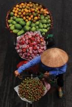 بائعة تحمل فواكه للبيع على دراجتها على طول شارع في هانوي فيتنام - ا ف ب