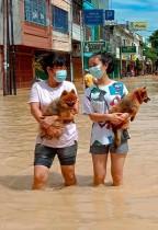 فتاتان تحملان كلبيهما وهما يخوضان في مياه الفيضانات في تيبينج تينجي، حيث غمرت المياه آلاف المنازل في شمال سومطرة الأندونيسية بعد هطول أمطار غزيرة على المنطقة.  ا ف ب
