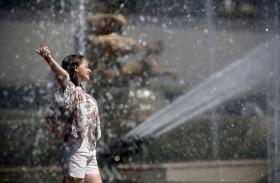 فتاة تستمع بمياه النافورة الباردة بعد ارتفاع درجات الحرارة هذا الصيف في باريس. ( رويترز)