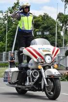 شرطية إندونيسية تقود دراجتها النارية بينما تؤدي التحية واقفة للتعبير عن مهاراتها مع بدء إجراء الانتخابات العامة في جاكرتا. أ ف ب