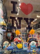 رجل يرتدي قناعاً للوجه وينظر من داخل نافذة متجر هدايا في ميدان التايمز مع استمرار تفشي فيروس كورونا في نيويورك. رويترز
