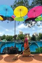 عاملة تسير تحت تركيب فني للمظلات الملونة بينما خففت الحكومة القيود وسط جائحة فيروس كورونا في مومباي.ا ف ب