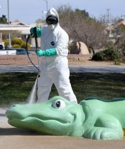 عامل يقوم بتطهير المعدات والألعاب في منتزه سينترنيال بمدينة لاس فيغاس خوفا من انتشار فيروس كورونا. (ا ف ب)