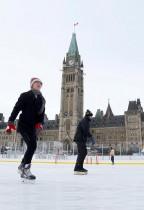 سيدتان تمارسان التزلج في طقس قارس البرودة في الهواء الطلق أمام البرلمان في أوتاوا، كندا.     (رويترز)