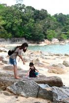 امرأة وطفلتها ترتديان أقنعة للوجه على شاطئ مهجور، مع استمرار الإغلاق الجزئي في ماليزيا وسط مخاوف من انتشار فيروس كورونا. ا ف ب